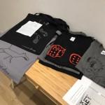 magliette con disegni dai quaderni di Luca Pozzi( grigia), Concetta Modica (nera),borse dai quaderni di An Paenhuysen (grigia) e Domenico Antonio Mancini (nera)